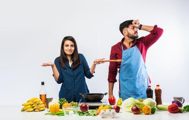부엌에서 인도 커플-신선한 야채와 과일을 많이 가진 남편과 함께 요리를 즐기는 젊은 아름 다운 아시아 아내