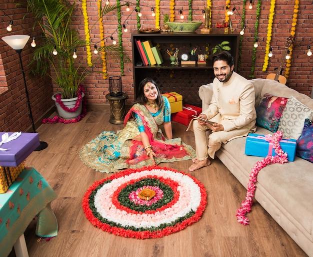 Индийская пара делает цветок ранголи на дивали или фестивале онам, делает селфи или держит сладости
