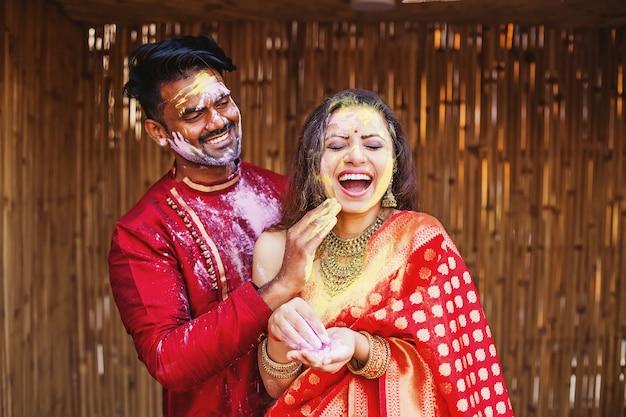 Holi를 연주하고 얼굴에 색을 칠하는 인도 커플
