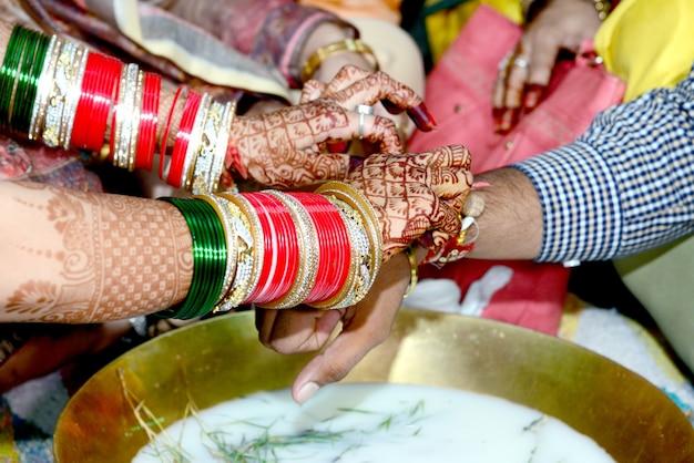 인도의 결혼식에서 링 낚시 게임을 하는 인도 커플