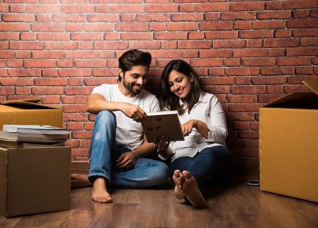 Индийская пара расслабляется во время переезда или распаковки дома, сидя между упаковочными коробками, глядя на фоторамку, мобильный телефон