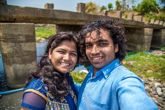 Selfieを取ってインドのカップル。川や滝のほとりで妻やガールフレンドと一緒にselfieを取る人。