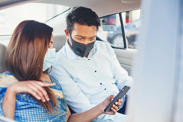 휴대 전화를 사용하여 택시에서 얼굴 마스크를 쓰고 인도 커플