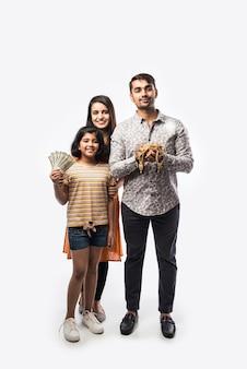 Индийская пара с милой дочерью держит золотые украшения, украшения