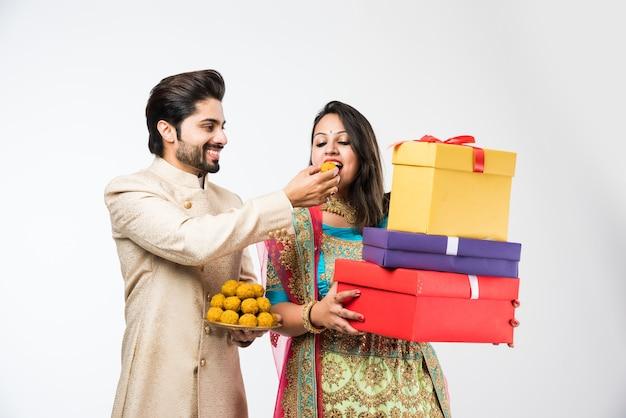 白い背景の上に孤立して立って、ディワリ祭やお祭りにラドゥーとギフトボックスを持つインドのカップル。伝統的な布を着て