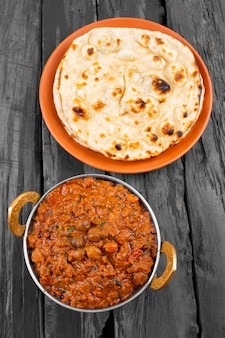 Indian cuisine chana masala served with tandoori roti on wooden background