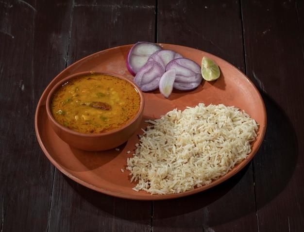 木製の背景にダルタッカとインド料理ジーラライス