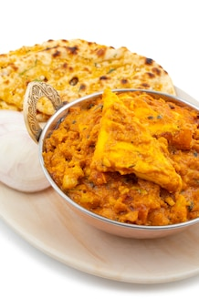 Indian cuisine special sweet and spicy paneer pasanda served with garlic naan on white background