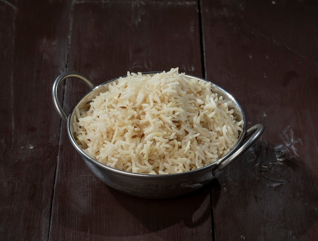 Indian cumin rice or jeera rice on wooden background