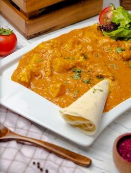 닭 가슴살과 토마토 소스를 곁들인 인도 카레는 lavash와 함께 제공됩니다.