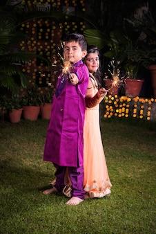 ディワリ祭の夜に線香花火またはfulzadiまたはphuljhadiで遊ぶ伝統的な服装のインドのかわいい男の子と女の子