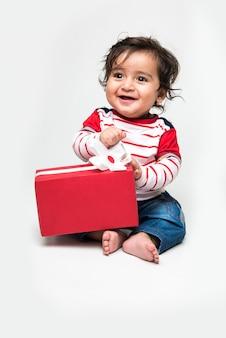 흰색 배경 위에 선물 상자를 들고 웃고 있는 인도의 귀여운 아기 소년 또는 유아 또는 유아