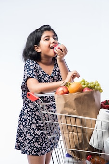 Индийская милая маленькая девочка с тележкой для покупок или тележкой, полной продуктов, овощей и фруктов, изолированные на белой стене