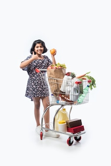 Indian cute little girlwith shopping cart or trolly full with grocery, vegetables and fruits, isolated over white wall