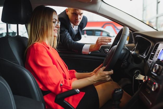 潜在的な顧客に車の機能を説明するインドのディーラー