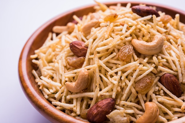 Indian deep fried falahari chivda also known as fasting or upwas chiwada made using potato and dry fruits for navaratri or any hindu vrat. served in a wooden bowl. selective focus Premium Photo
