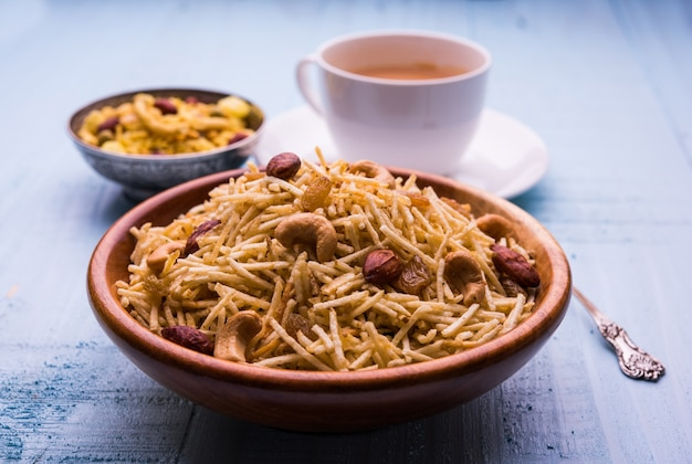 Indian deep fried falahari chivda also known as fasting or upwas chiwada made using potato and dry fruits for navaratri or any hindu vrat. served in a wooden bowl. selective focus