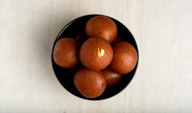 Indian dessert or sweet dish : gulab jamun in bowl on wooden background.