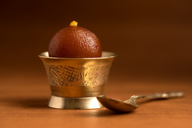 Indian dessert or sweet dish : gulab jamun in copper antique bowl with spoon