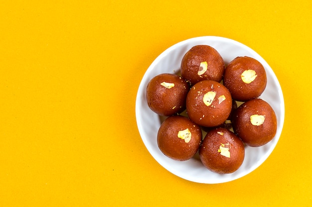 Indian dessert or sweet dish : gulab jamun in white bowl on yellow background