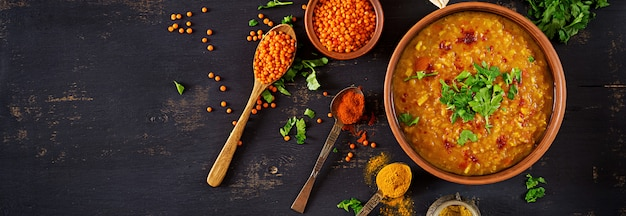 Indian dhal spicy curry in bowl, spices, herbs, rustic black wooden table.