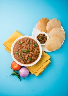 Индийское блюдо, острое карри из нута и гороха, также известное как чола или чана масала или обычно чоле, подается с жареными пури или пури на красочном или деревянном фоне. выборочный фокус