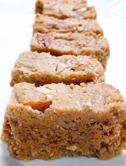 インドのディワリ菓子カラカンドは、ハルワまたはマワカラカンドとも呼ばれ、ラジャスタン州アルワルで生まれたパニールまたはカッテージチーズから作られたクリーミーな珍味です。白い背景で隔離