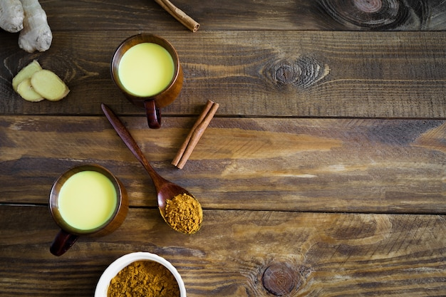 Indian drink golden milk in two wooden cups with ingredients ginger, turmeric on a wooden spoon and cinnamon sticks top view on a wooden background with copy space.