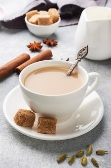 Indian drink masala tea with milk and spices. cardamom sticks cinnamon star anise cane sugar.