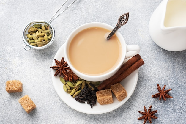 Indian drink masala tea with milk and spices. cardamom sticks cinnamon star anise cane sugar.