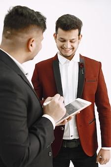 프로젝트에서 작업하는 인도 임원. 그의 동료에 게 뭔가 보여주는 태블릿 남자.