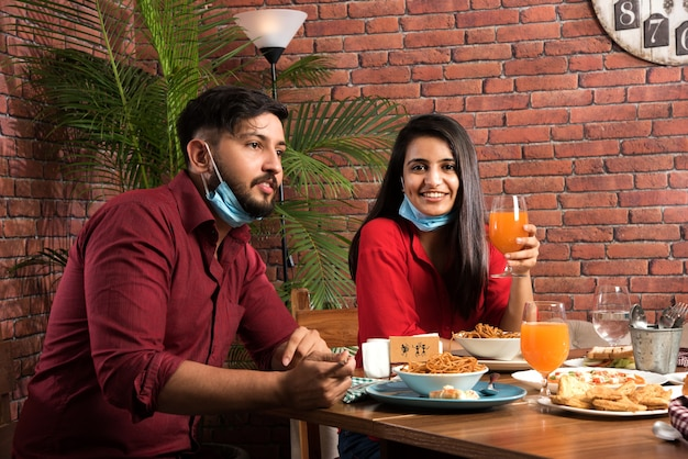 코로나 전염병이 인도의 새로운 정상적인 생활 방식을 보여주는 개념을 잠금 해제 한 후 식당에서 음식을 먹는 동안 인도 가족과 친구들이 얼굴 마스크를 착용