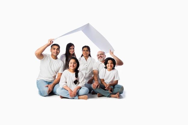 Индийская семья и концепция недвижимости - азиатская семья из нескольких поколений держит модель бумажного дома с ключами у белой стены