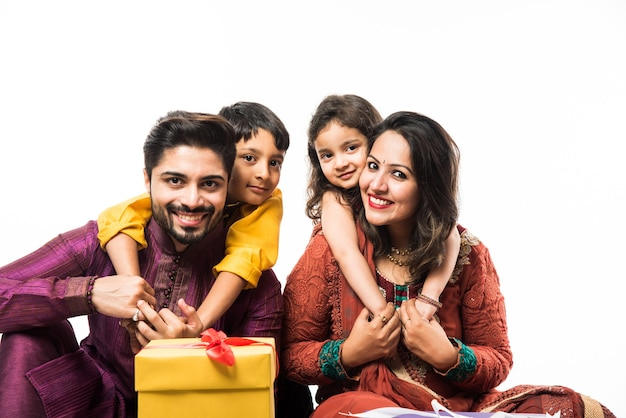 ターリーのギフトボックスとランプで白い背景の上に孤立して座っている間、伝統的な服でディワリ祭またはディーパバリ祭を祝うインドの家族