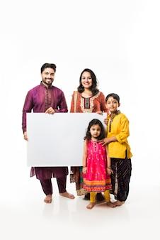 空白のホワイトボードまたはプラカードを保持しながらディワリ祭を祝うインドの家族。白い背景の上に孤立して立って、カメラを見て