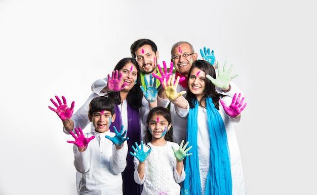 Индийская семья празднует фестиваль холи со сладкими подарками ладду и цветами в тарелке. изолированные на белом фоне. значение выборочного фокуса