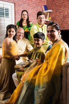 Индийская семья празднует ракша бандхан или фестиваль ракхи дома в традиционной одежде и сидит на диване