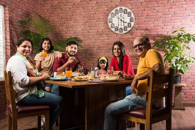 Индийская семья ест еду за обеденным столом дома или в ресторане вместе