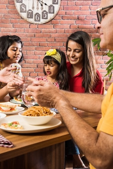 Indian family eating food at dining table at home or restaurant having meal together