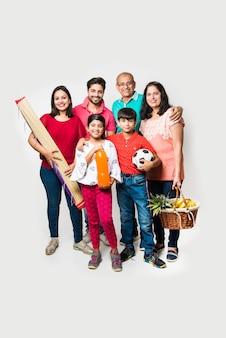 ピクニックに行くインドの家族-フルーツバスケット、マット、サッカー、飲み物で白い背景の上に立っているアジアの家族の多世代。セレクティブフォーカス
