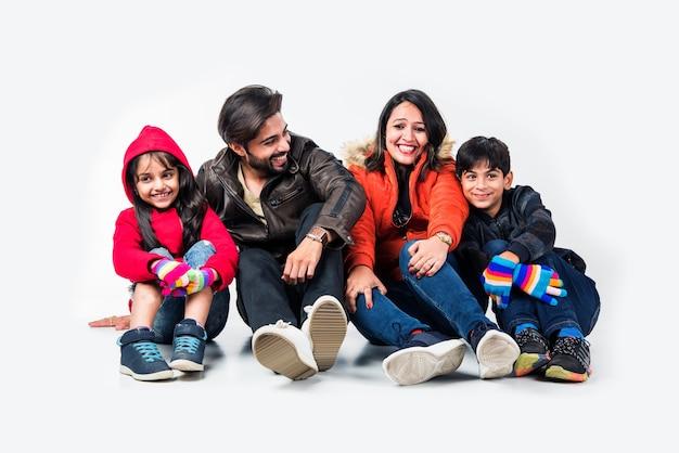白い背景に座って暖かい服を着たインドの家族。冬の準備ができて