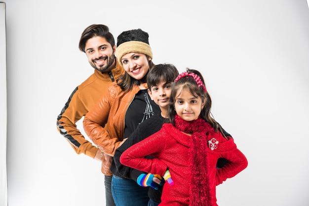 白い背景に立っている暖かい服を着たインドの家族。冬の準備ができて