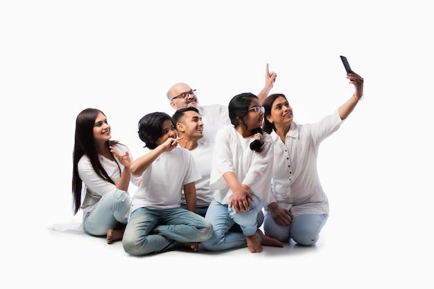 스마트 폰으로 전화를 걸거나 백인에 대해 셀카 사진을 찍는 6 명의 영상의 인도 가족