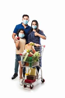 Индийская семья за покупками с детьми во время вспышки вируса. мать, отец и дочь в хирургической маске покупают продукты в супермаркете. семья в магазине.