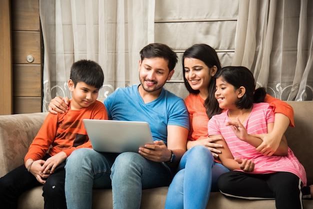 Индийская семья сидит на диване и использует ноутбук, сидя на диване у себя дома