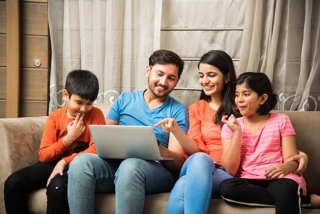 Индийская семья сидит на диване и с помощью смартфона, ноутбука или планшета смотрит фильм или просматривает интернет
