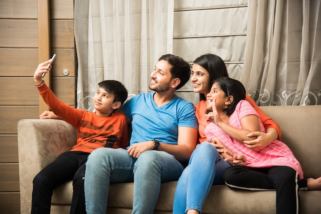 Indian family sitting on sofa and using smartphone laptop or tablet watching movie or surfing internet