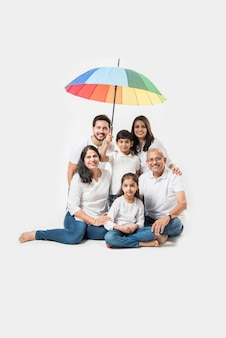 Indian family sitting with umbrella over white background. selective focus