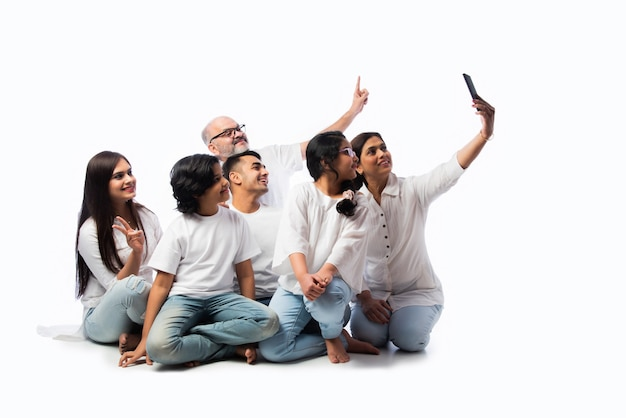 Indian family of six video calling on smartphone or taking selfie picture against white