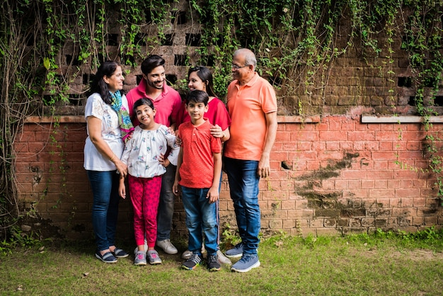 Индийская семья, стоящая в очереди у стены, покрытой лианами. несколько поколений азиатской семьи в парке или саду веселятся, концепция здоровой семейной жизни